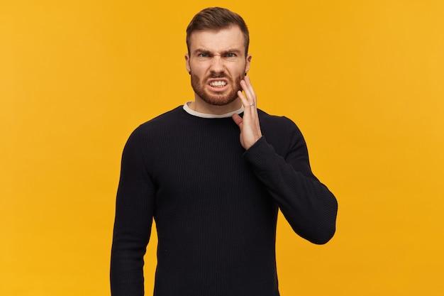 Boze, gekke jongeman met baard in zwarte longsleeve kijkt geïrriteerd en raakt zijn wang aan over gele muur