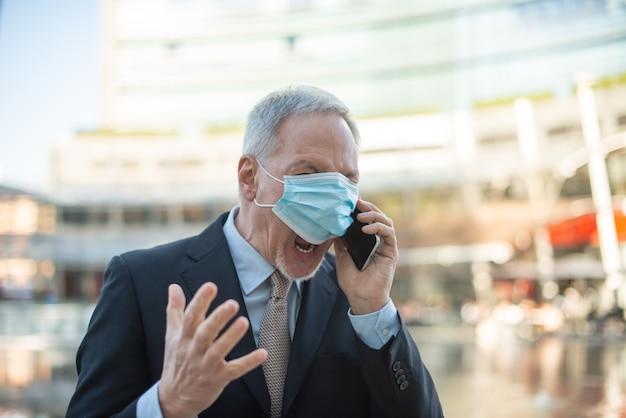 Boze gemaskerde senior zakenman die schreeuwt naar de telefoon buiten, covid en coronavirus concept