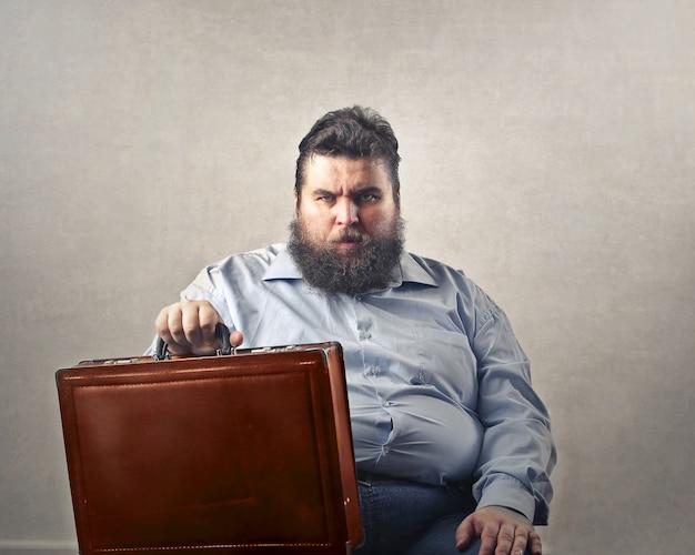 Boze grote bebaarde man zit en houdt een koffer op zijn schoot