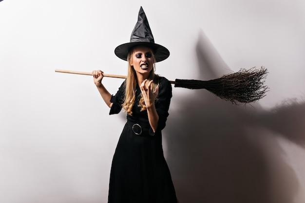 Boze heks die aan iets slechts denkt. vrouwelijke tovenaar in lange zwarte jurk die woede uitdrukt in halloween.