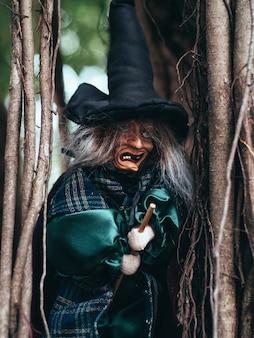 Boze heks op de donkere achtergrond van de natuur, close-up portret van oude dame met angstaanjagende make-up, halloween-achtergrond
