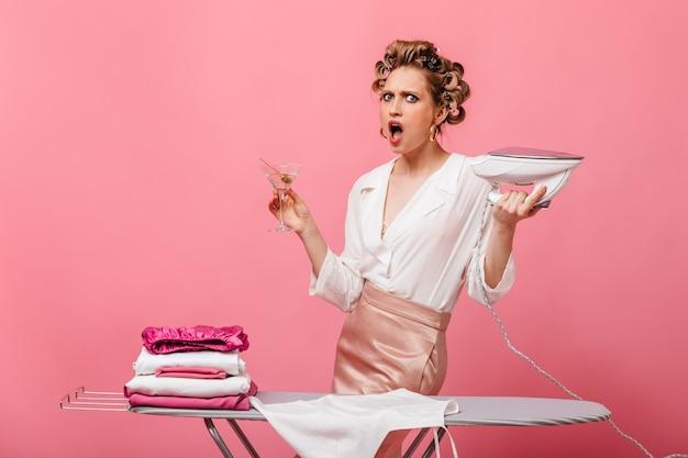 Boze huisvrouw in zakelijke outfit met ijzer en martiniglas