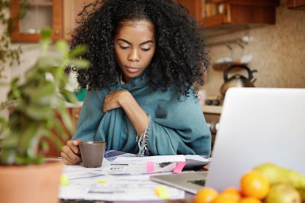Boze huisvrouw met donkere huid en afro-kapsel die koffie drinkt terwijl ze 's avonds laat het binnenlandse budget beheert