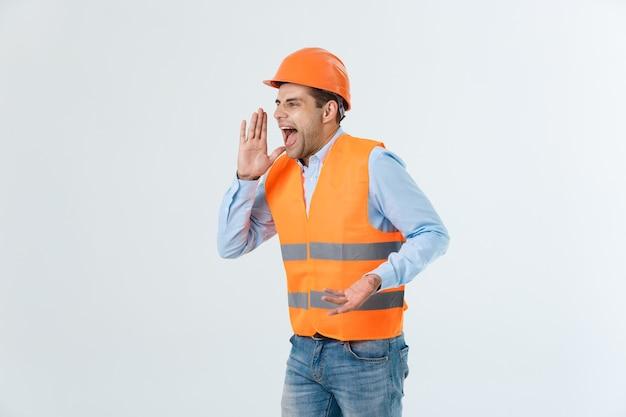 Boze ingenieur met boze gezichtsemotie die schreeuwt tegen iemand die zijn beide handen opheft, geïsoleerd op een witte achtergrond.