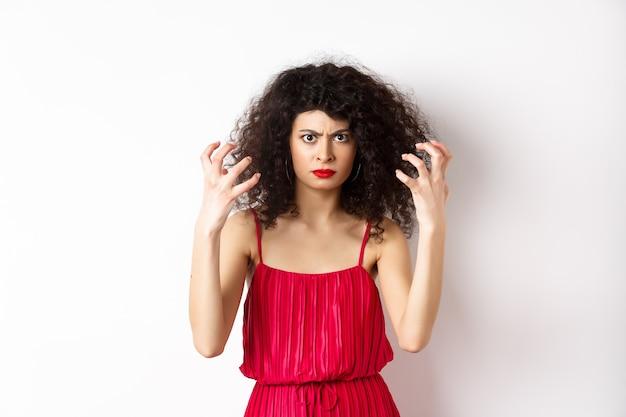 Boze italiaanse vrouw met krullend haar en rode jurk, kokend van woede, fronsen en balde handen woedend, staande op een witte achtergrond.
