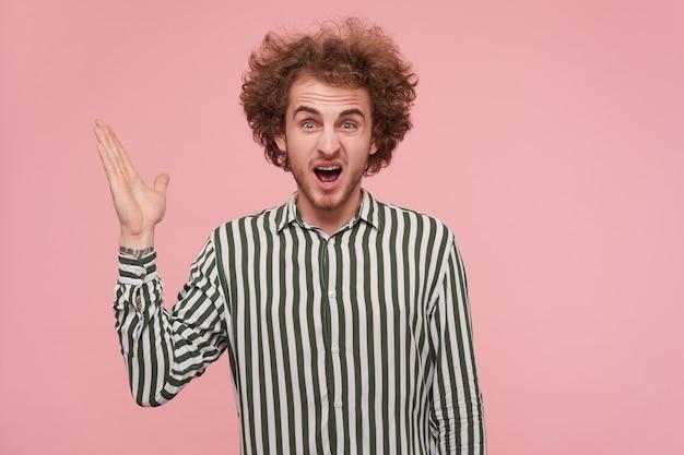 Boze jonge, bebaarde, gekrulde man die emotioneel zijn handpalm opheft terwijl hij schreeuwend schreeuwt en zijn wenkbrauwen fronst, gekleed in een gestreept shirt terwijl hij over de roze muur staat