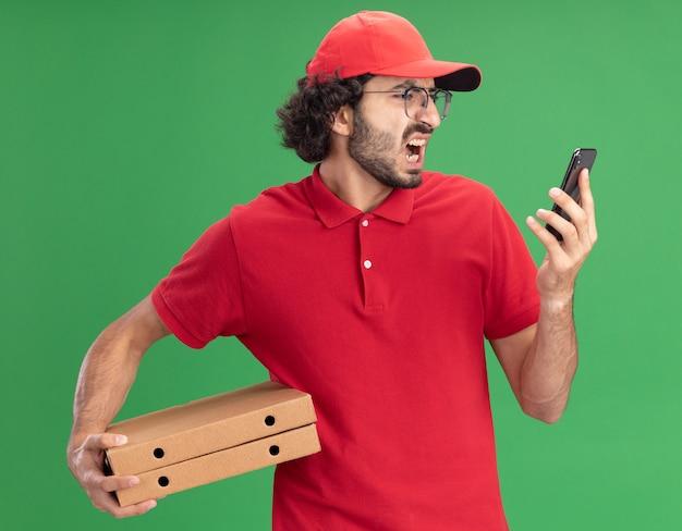 Boze jonge blanke bezorger in rood uniform en pet met een bril met pizzapakketten en mobiele telefoon die naar de telefoon kijkt