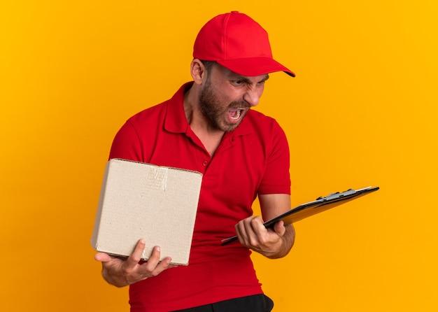 Boze jonge blanke bezorger in rood uniform en pet met klembord en kartonnen doos kijkend naar klembord schreeuwend geïsoleerd op oranje muur