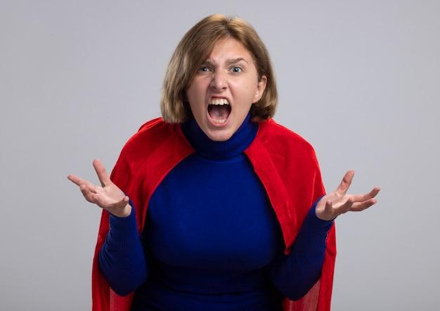 Boze jonge blonde supervrouw in rode cape die lege handen toont die voorzijde bekijken die op witte muur wordt geïsoleerd