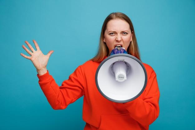 Boze jonge blonde vrouw die lege hand toont die door spreker spreekt