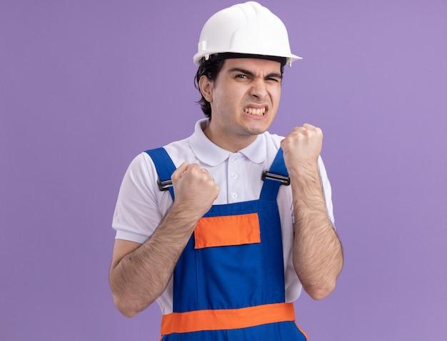 Boze jonge bouwersmens in bouwuniform en veiligheidshelm die geïrriteerde en geïrriteerde vuisten balanceren die zich over purpere muur bevinden