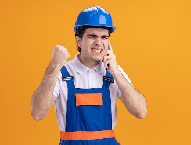 Boze jonge bouwersmens in eenvormige bouw en veiligheidshelm die op mobiele telefoon spreken die zich over oranje muur bevindt