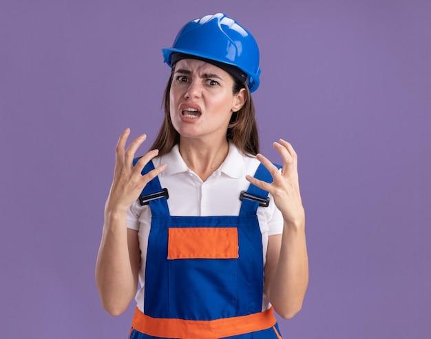 Boze jonge bouwersvrouwen in eenvormige hand in hand rond gezicht dat op purpere muur wordt geïsoleerd