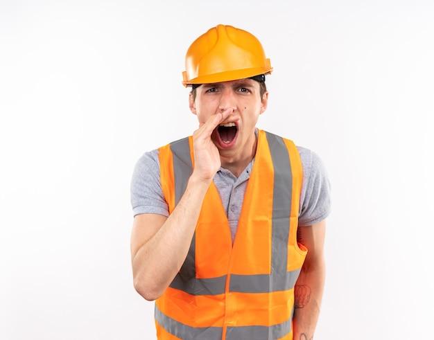 Boze jonge bouwman in uniform die iemand belt