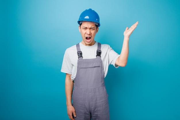 Boze jonge bouwvakker die veiligheidshelm draagt en eenvormig die lege hand toont