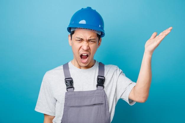 Boze jonge bouwvakker die veiligheidshelm en eenvormig draagt die het lege hand schreeuwen toont