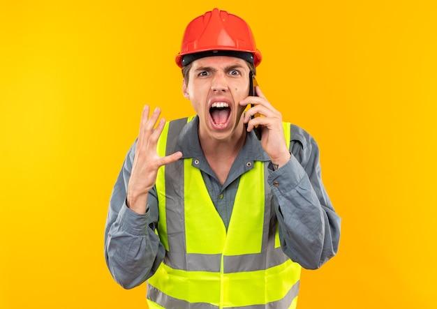 Boze jonge bouwvakker in uniform spreekt aan de telefoon