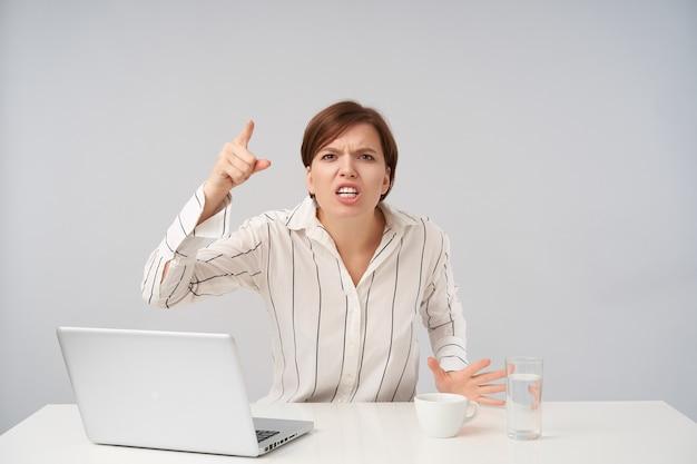Boze jonge bruinogige kortharige vrouw met natuurlijke make-up opgewonden wijsvinger verhogen terwijl verhit kijken, zittend aan tafel op wit