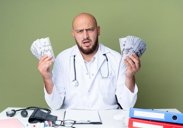Boze jonge kale mannelijke arts met een medisch gewaad en een stethoscoop die aan het bureau zit