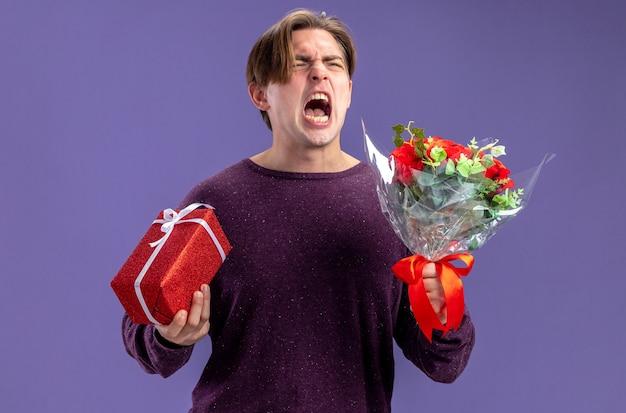 Boze jonge kerel op valentijnsdag met geschenkdoos met boeket geïsoleerd op blauwe achtergrond