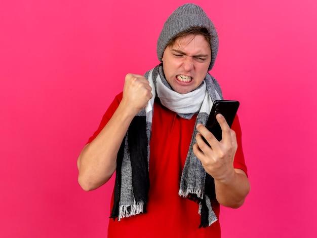 Boze jonge knappe blonde zieke man die de winterhoed en sjaal draagt die mobiele telefoon en servet houdt die telefoon bekijkt die op roze muur wordt geïsoleerd