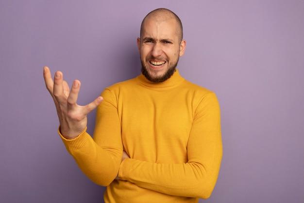 Boze jonge knappe kerel die hand standhoudt die op purpere muur met exemplaarruimte wordt geïsoleerd