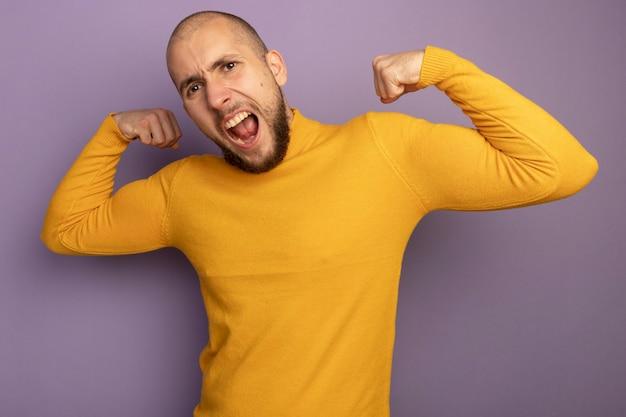 Boze jonge knappe kerel die sterk gebaar toont dat op purpere muur wordt geïsoleerd