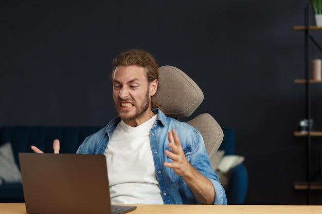 Boze jonge knappe krullende man met behulp van laptop. gestresste freelancer verloor gegevens op kapotte niet-werkende laptop. slecht nieuws of e-mail ontvangen, spambericht. jongeren die met mobiele apparaten werken.