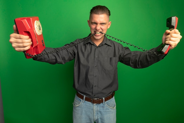 Boze jonge knappe man in grijs shirt met vintage telefoon bijtende koord staande over groene muur