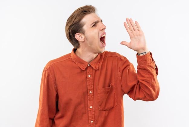 Boze jonge knappe man met een rood shirt die iemand belt die op een witte muur is geïsoleerd