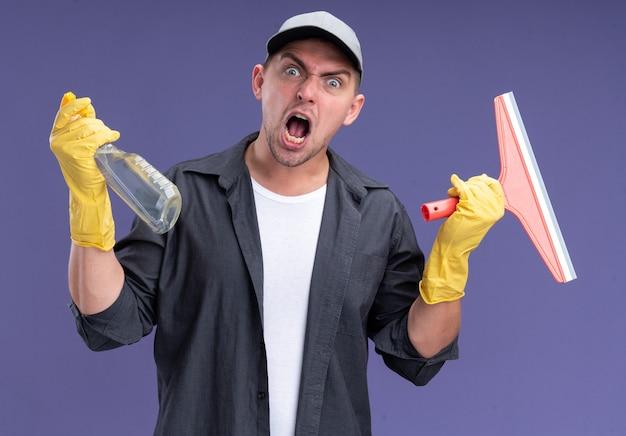 Boze jonge knappe schoonmaakster die t-shirt met pet en handschoenen draagt die zwabberhoofd en spuitfles houden die op purpere muur wordt geïsoleerd