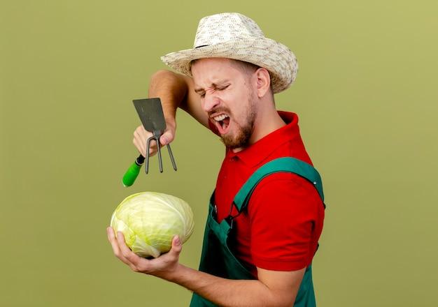 Boze jonge knappe slavische tuinman in uniform en hoed staande in profielweergave houden kijken naar kool houden schoffel-hark erboven in een andere hand geïsoleerd
