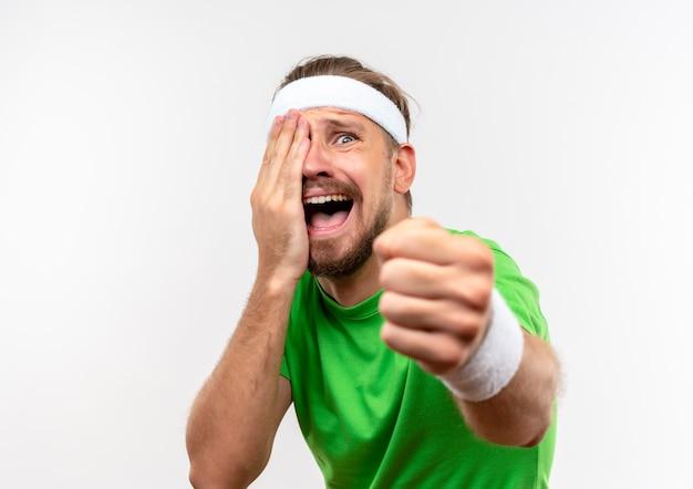Boze jonge knappe sportieve man met hoofdband en polsbandjes die de hand op het gezicht zetten en de vuist uitstrekken die op een witte muur is geïsoleerd