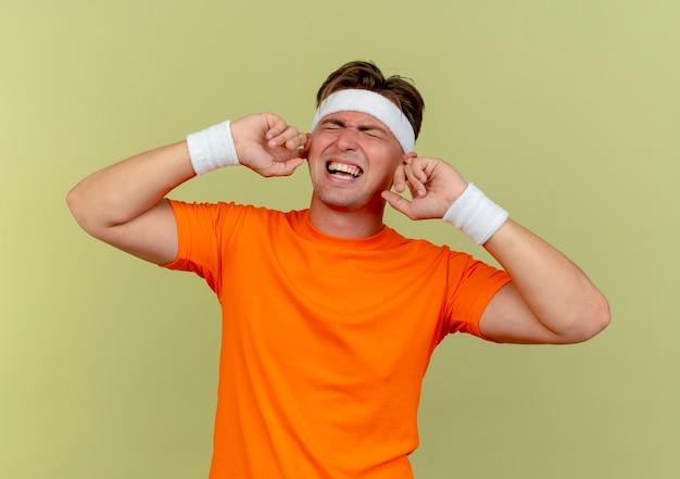 Boze jonge knappe sportieve man met hoofdband en polsbandjes vingers in de oren met gesloten ogen geïsoleerd op olijfgroen