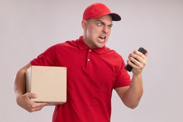 Boze jonge leveringsmens die eenvormig met de doos van de glbholding draagt en telefoon in zijn hand bekijkt die op witte muur wordt geïsoleerd