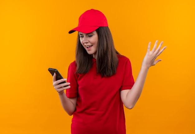 Boze jonge leveringsvrouw die rode t-shirt in rood glb draagt die een telefoon op geïsoleerde gele muur houdt
