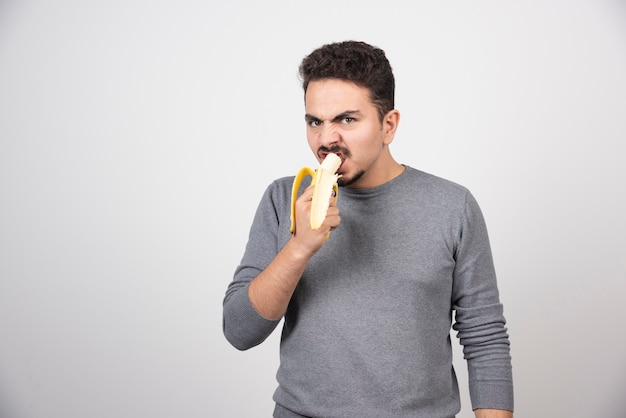 Boze jonge man die een banaan eet over een witte muur.