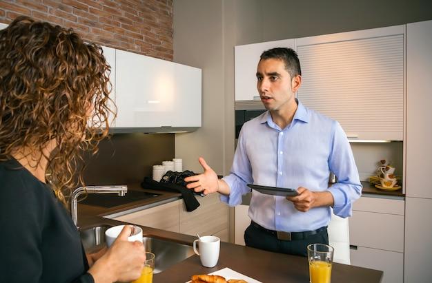 Boze jonge man die een elektronische tablet vasthoudt terwijl hij ruzie maakt met een gekrulde vrouw bij het ontbijt thuis