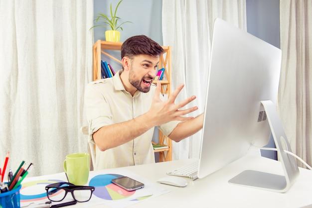 Boze jonge man die op zijn computer gilt