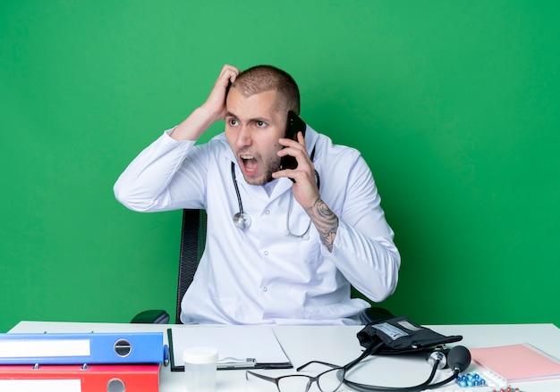 Boze jonge mannelijke arts het dragen van medische mantel en stethoscoop zittend aan een bureau met uitrustingsstukken praten over de telefoon zetten hand op hoofd kijken kant geïsoleerd op groen