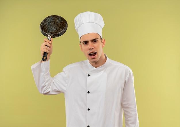 Boze jonge mannelijke kok die eenvormige chef-kok draagt die koekenpan in zijn hand op geïsoleerde groene muur opheft