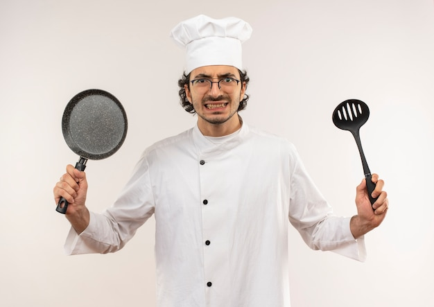 Boze jonge mannelijke kok die eenvormige chef-kok en glazen draagt die pan en spatel houden