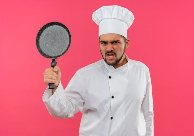 Boze jonge mannelijke kok in uniform van de chef-kok met koekenpan geïsoleerd op roze muur
