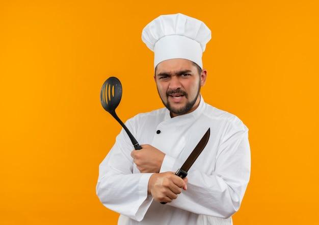 Boze jonge mannelijke kok in uniform van de chef-kok met mes en lepel met sleuven geïsoleerd op een oranje muur met kopieerruimte