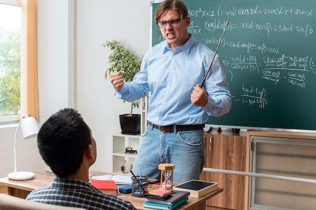 Boze jonge mannelijke leraar met een bril die gefrustreerd kijkt terwijl hij de les aan leerlingen uitlegt, in de buurt van het bord met wiskundige formules in de klas