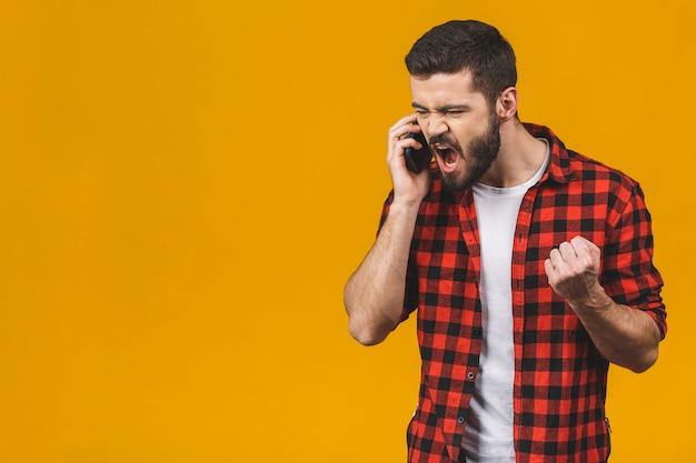 Boze jonge mens die op de celtelefoon gilt die op een gele muur wordt geïsoleerd.