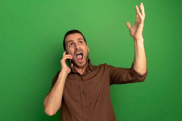 Boze jonge mens die op telefoon spreekt die hand omhoog kijkt die omhoog geïsoleerd op groene muur kijkt