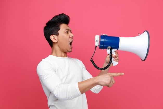 Boze jonge mens die zich in profielmening bevindt die en naar kant kijkt die in luide spreker schreeuwt
