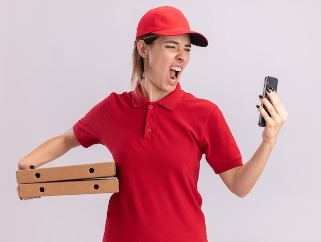 Boze jonge mooie levering meisje in uniform houdt pizzadozen en kijkt naar de telefoon op wit