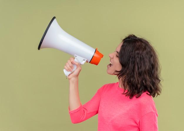 Boze jonge mooie vrouw die door spreker spreekt die zich in profielmening over geïsoleerde groene muur bevindt